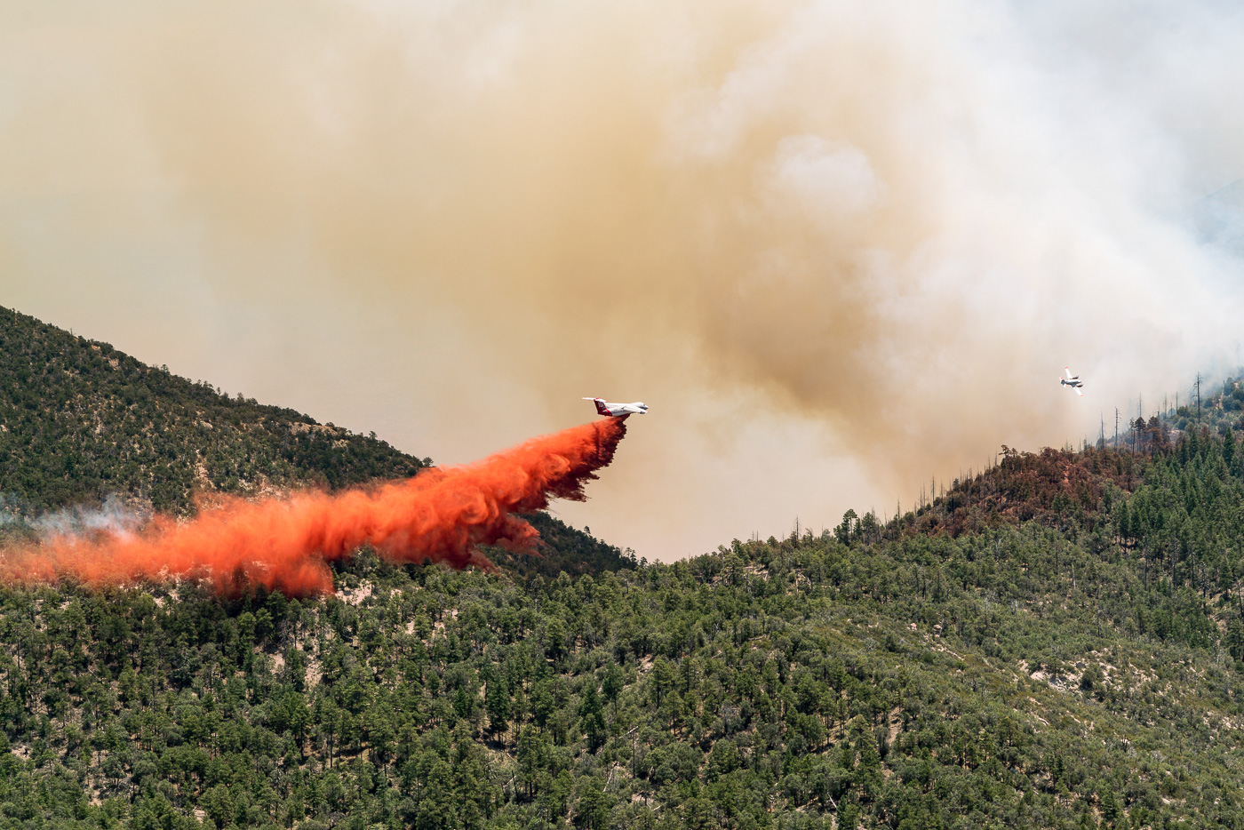 Airplanes drop fire retardant on flames trying to come over a ridge - near Guthrie Mountain. July 2017.